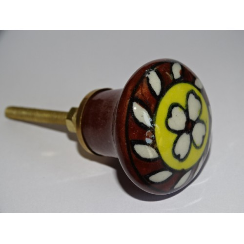 brown and yellow porcelain button with white flower